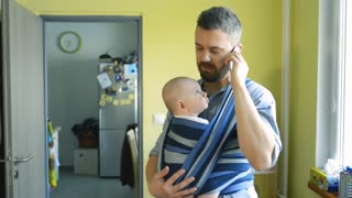 Young father at home with his newborn baby son in sling holding smart phone, making phone call, talking