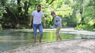 Young father with little boy at the river, sunny spring day.