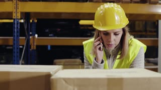Young female warehouse worker with smartphone. A supervisor standing near pallet truck with boxes, making a phone call