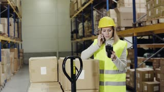 Young female warehouse worker with smartphone. A woman supervisor standing near pallet truck with boxes, making phone call