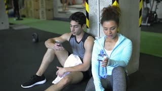 Young fit couple in gym resting, drinking water.