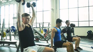 Young fit men in gym working out with weights.