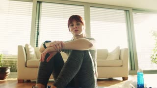 Young fitness woman with smartwatch at home sitting on the floor and resting.