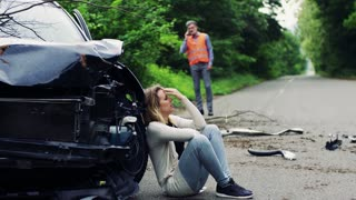 Young frustrated woman by the car after an accident and a man with smartphone, making a phone call.