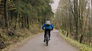 Young handsome man riding his bicycle outside in autumn nature. Rear view. Slow motion