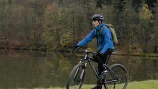 Young handsome man riding his bicycle outside in autumn nature