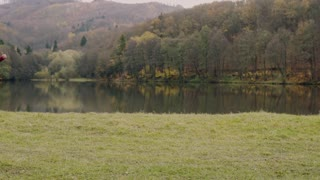 Young handsome man running by the lake in autumn nature. Slow motion