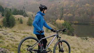 Young handsome man with a bicycle outside in autumn nature. Slow motion