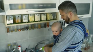 Young hipster father with his little baby son in sling at home, washing dishes