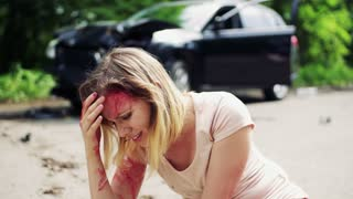 Young injured bleeding woman on the road unable to get up after a car accident.