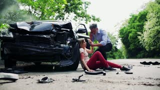 Young injured woman by the car after an accident and a man with smartphone, making a phone call. Slow motion.