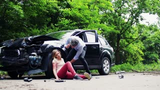 Young injured woman by the car after an accident and a man with smartphone, making a phone call.