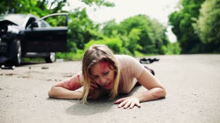 Young injured woman lying on the road in front of a damaged car after a car accident, making a phone call. Slow motion.