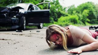 Young injured woman lying on the road in front of a damaged car after a car accident, making a phone call.
