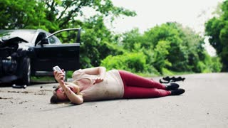 Young injured woman lying on the road in front of a damaged car after a car accident, throwing away a broken telephone.