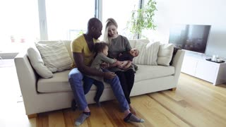 Young interracial family with little children at home.
