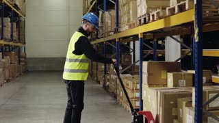 Young male warehouse worker loading hand pallet truck with boxes