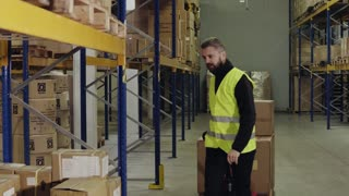 Young male warehouse worker pulling a pallet truck and unloading boxes