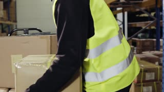 Young male warehouse worker unloading boxes from a hand pallet truck
