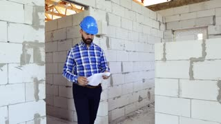 Young man at the construction site, looking at plans of the new house, checking and controlling.