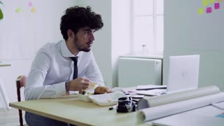 Young man having lunch in an office.