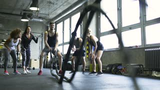 Young man in crossfit gym working out with battle ropes.