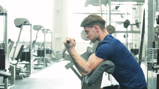Young man in gym working out, using weights machine for arms.