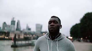 Young sporty black man runner with earphones and smart phone in arm band running on the bridge outside in a city. Slow motion.