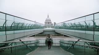 Young sporty black man runner with smart phone in arm band running on the bridge outside in a London city, St. Paul's cathedral in the background. Slow motion.