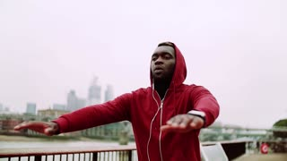 Young sporty black man runner with smartwatch and earphones exercising on the bridge outside in a London city. Slow motion.