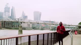 Young sporty black man runner with smartwatch and earphones running on the bridge outside in a London city. Slow motion.
