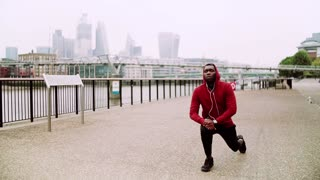 Young sporty black man runner with smartwatch and earphones stretching on the bridge outside in a London city. Slow motion.
