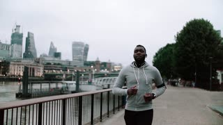 Young sporty black man runner with smartwatch, earphones and smart phone in arm band running on the bridge outside in a city. Slow motion.