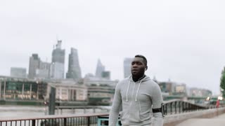 Young sporty black man runner with smartwatch, earphones and smart phone in arm band running on the bridge outside in a city.