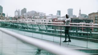 Young sporty black man runner with smartwatch, earphones and smartphone in an armband on the bridge in a city, resting. Slow motion.
