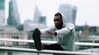 Young sporty black man runner with smartwatch, earphones and smartphone in an armband on the bridge in a city, stretching. Slow motion.