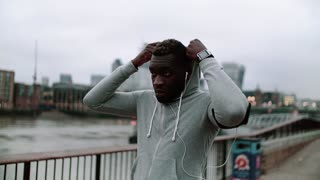 Young sporty black runner with smartwatch and earphones on the bridge in a London city, resting. A man putting a hood on head. Slow motion.