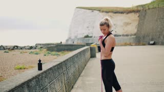 Young sporty woman runner doing exercise with elastic rubber bands outside on a beach in nature.