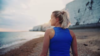 Young sporty woman runner in blue sportswear walking outside on the beach in nature. Copy space. Slow motion.