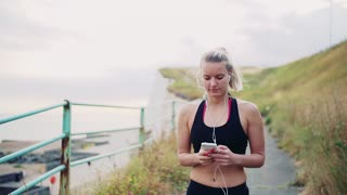 Young sporty woman runner walking outside on the beach in nature, using smartphone. Slow motion.