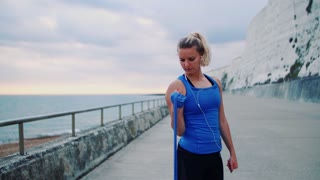 Young sporty woman runner with earphones doing exercise with elastic rubber bands outside on a beach in nature.