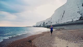 Young sporty woman runner with earphones in blue sportswear running outside on the beach in nature. Copy space. Slow motion.