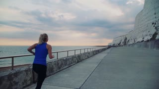 Young sporty woman runner with earphones running by the sea outside in nature, listening to music. Rear view. Slow motion.