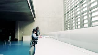 Young student boy in a wheelchair and his teacher studying in a library.