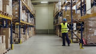 Young warehouse workers pulling a pallet truck with boxes. Slow motion