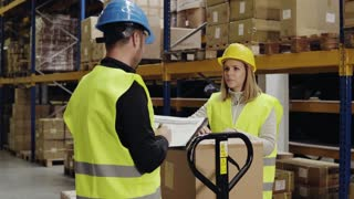 Young warehouse workers working together. Man and woman discussing something, making notes
