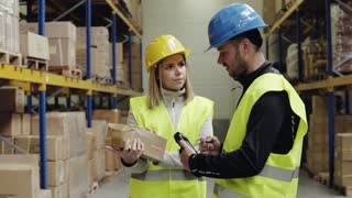 Young warehouse workers working together. Man and woman discussing something