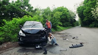 Young woman by the car after an accident and a man with smartphone, making a phone call.