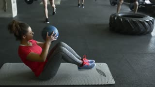 Young woman in crossfit gym working out her abs.