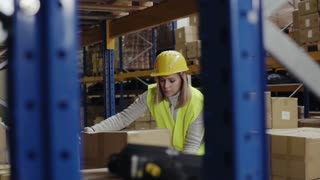 Young woman warehouse worker loading a pallet truck with boxes. Slow motion